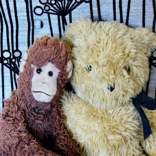Two soft toys, a bear and a monkey, on an armchair upholstered in gorgeous Warwick fabric