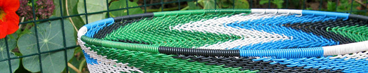 The top rim of a telephone-wire basket in a chevron pattern of green, black, blue and white