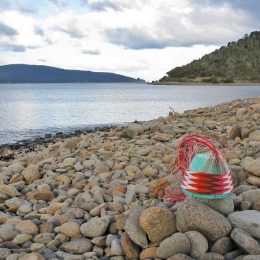 Telephone-wire basket, with chevron pattern, on the pebble beach at Cockle Bay Lagoon. Maria Island is in the background.