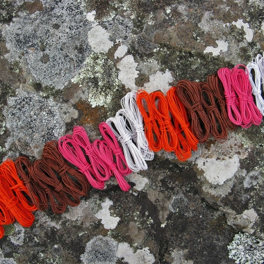 Coils of white, orange, brown and pink telephone wire on a lichen-covered rock at Hellfire Bluff in Tasmania.