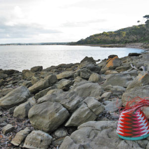 Fab-40 wire basket, with white, orange, brown and pink wires in a zig-zag pattern, on the rocky beach at American River on Kangaroo Island.