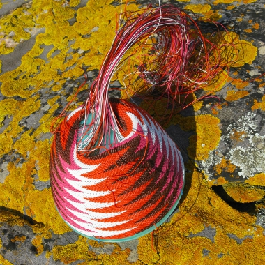 Pink, orange, brown and white wire basket in progress on a grey rock covered in bright orange-yellow lichen.