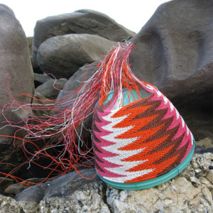 Close-up of a chevron-patterned telephone-wire basket nestled on the glistening rocks at Antechamber Bay, Kangaroo Island.