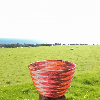 The finished chevron-patterned basket on a fence post, with sheep grazing in a grassy paddock with the sea in the background.