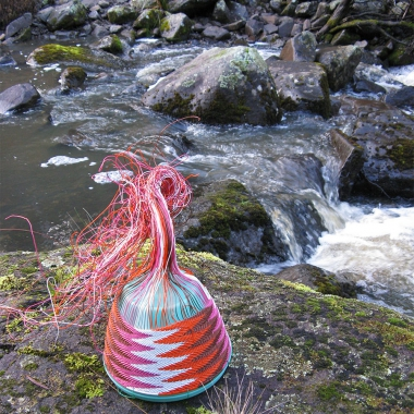 Chevron-patterned wire basket on lichen and moss covered rocks alongside a creek at Lemont, Tasmania.