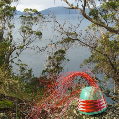 Telephone wire basket on a lichen-covered rock at Whalers Lookout, with a view of Maria Island in the distance.