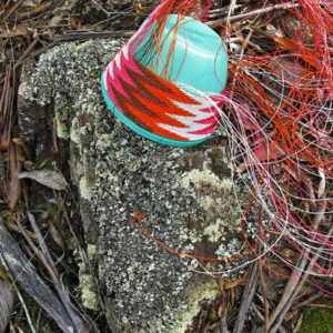 Pink, brown, orange and white telephone wire basket in progress, on a lichen-covered rock at Whalers Lookout, Tasmania.