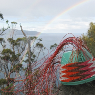 A chevron-patterned telephone wire basket on a stump of wood, with a view of Maria Island in the distance and a rainbow overhead.
