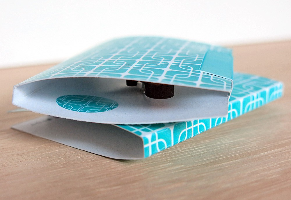 The easel-style card stand folds into a sweet little patterned turquoise and white gift box