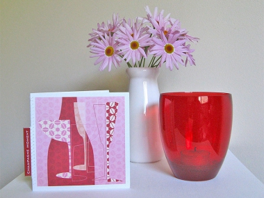 A greeting card of an abstract image of a champagne bottle and glasses, next to a vase of pink daisies and a red glass.