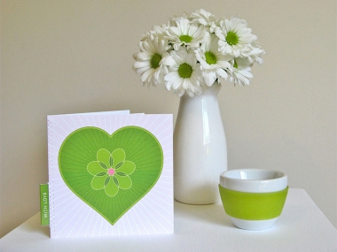 A greeting card featuring a big green heart with a floral shape in the centre, against a pale pink starburst in front of a vase of white chrysanthemums.