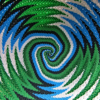 Close-up of the inside of a telephone wire basket, in a spiralling, chevron pattern of white, blue, black and metallic green wires.