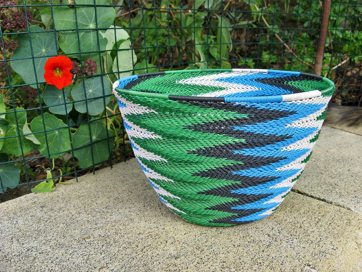 A completed telephone wire basket in a chevron pattern of blue, black, white and metallic green wires.