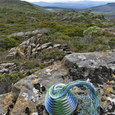 Wire basket on lichen covered rocks, looking out to Lake Daphne from the foot of Wyld's Craig in Tasmania's South-West.