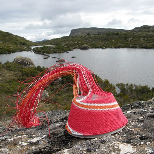 Red, pink, white and orange wire basket on a rock, with view of Long Tarns (Central Plateau, Tasmania) in the background