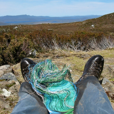 Telephone wire basket in progress, with a view of the Cradle Mountain - Lake St Clair National Park in the distance.