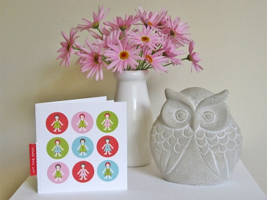 A happy, feminine greeting card in pink, green, blue and green of little girls arranged in a 3 by 3 grid, next to a small owl statuette and a vase of pink daisies.