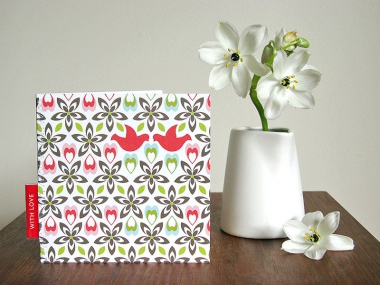Greeting card showing two red doves facing each other amidst a repeating pattern of hearts and flowers in red, pink, green, pale blue and black, next to a small vase of lilies.