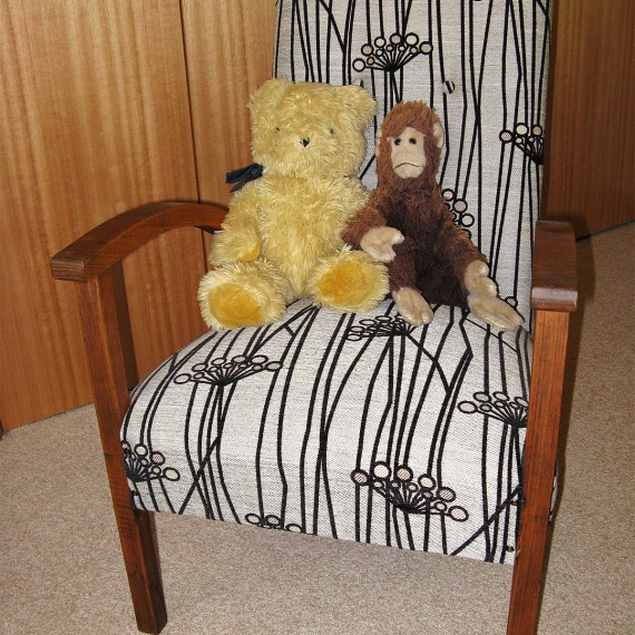 A soft toy monkey and a teddy bear placed together on an armchair