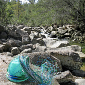 Telephone wire basket in progress, on the rocky shores of North West Bay River, near Cathedral Rock, Tasmania.