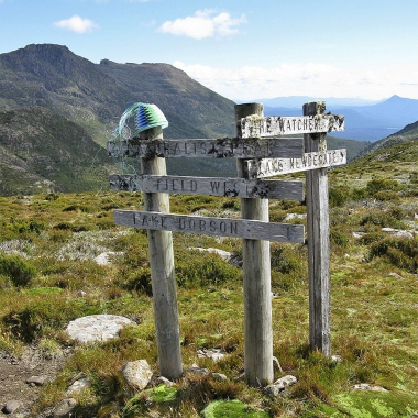 Telephone wire basket on a signpost pointing to Naturaliste Peak, Mt Field West and Lake Dobson, with Naturaliste Peak and Mt Field West in the background.
