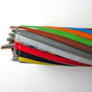 A close-up of the brightly coloured, helically arranged plastic tubes that enclose optic fibres, showing the sticky water-repellent gel.