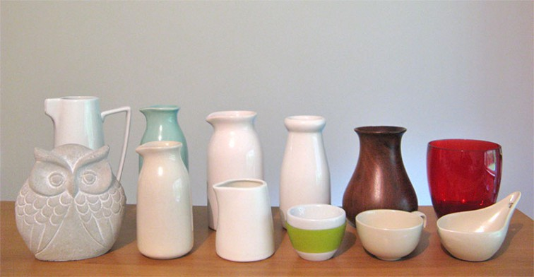 A selection of wood, ceramic and glass vases, cups, jugs and jars, and a pale grey plaster-cast owl, arranged in two rows from tallest to shortest.