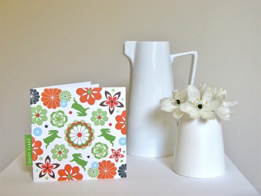 Greeting Card in a fresh colourway of orange, green, sky blue and black, next to a white jug and a small vase of white lilies.
