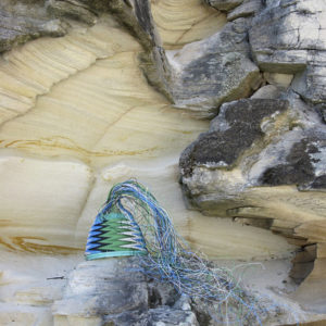 Telephone wire basket in progress, resting on sandstone rocks at Adventure Bay, Bruny Island, Tasmania.