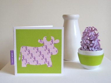 A fun card of a patterned purple cow against a bright green background, with a stitched-in label that reads