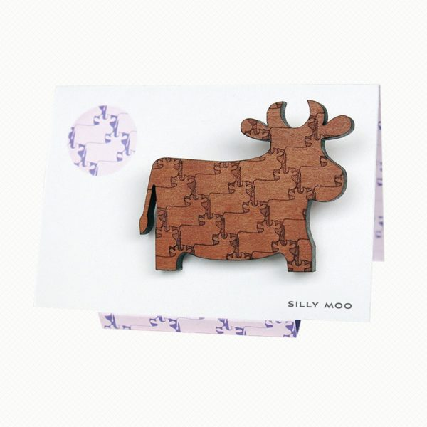 Cow brooch in Tasmanian Myrtle wood with a delicately engraved pattern of overlapping cows, on an easel-style card with a matching purple and white pattern