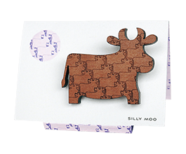 Cow brooch in Tasmanian Myrtle wood with a delicately engraved pattern of overlapping cows, on an easel-style card in a matching purple and white pattern