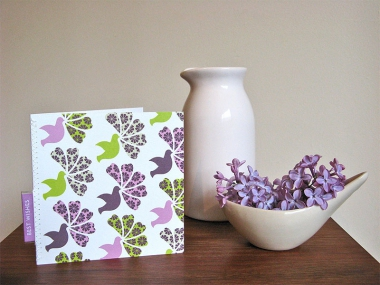 A greeting card with a purple and green pattern of doves and flowers and a stitched-in label that reads