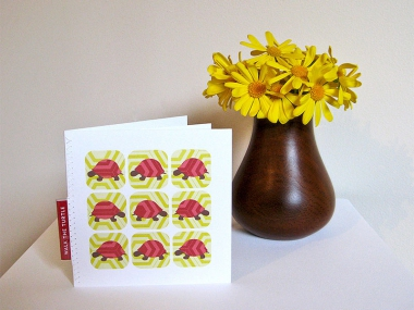 Greeting card showing tiles of pink, red and brown turtles in a 3 by 3 grid on a yellow hexagon pattern, standing next to a wooden vase of yellow daisies.