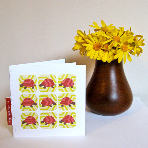 Walk the Turtle greeting card standing in front of a dark brown wooden vase with deep yellow daisies