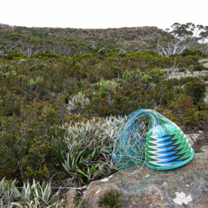 Telephone-wire basket on lichen-covered rocks with the top of Mt Wellington, from the South, in the background.