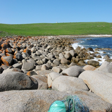 The basket in its very early stages on granite rocks at Windmill Bay, with the Cape Willoughby lighthouse in the background.