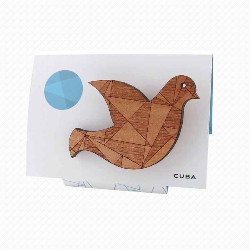 Chic wooden dove brooch in a mid-century modern style with a delicately laser-engraved geometric pattern.